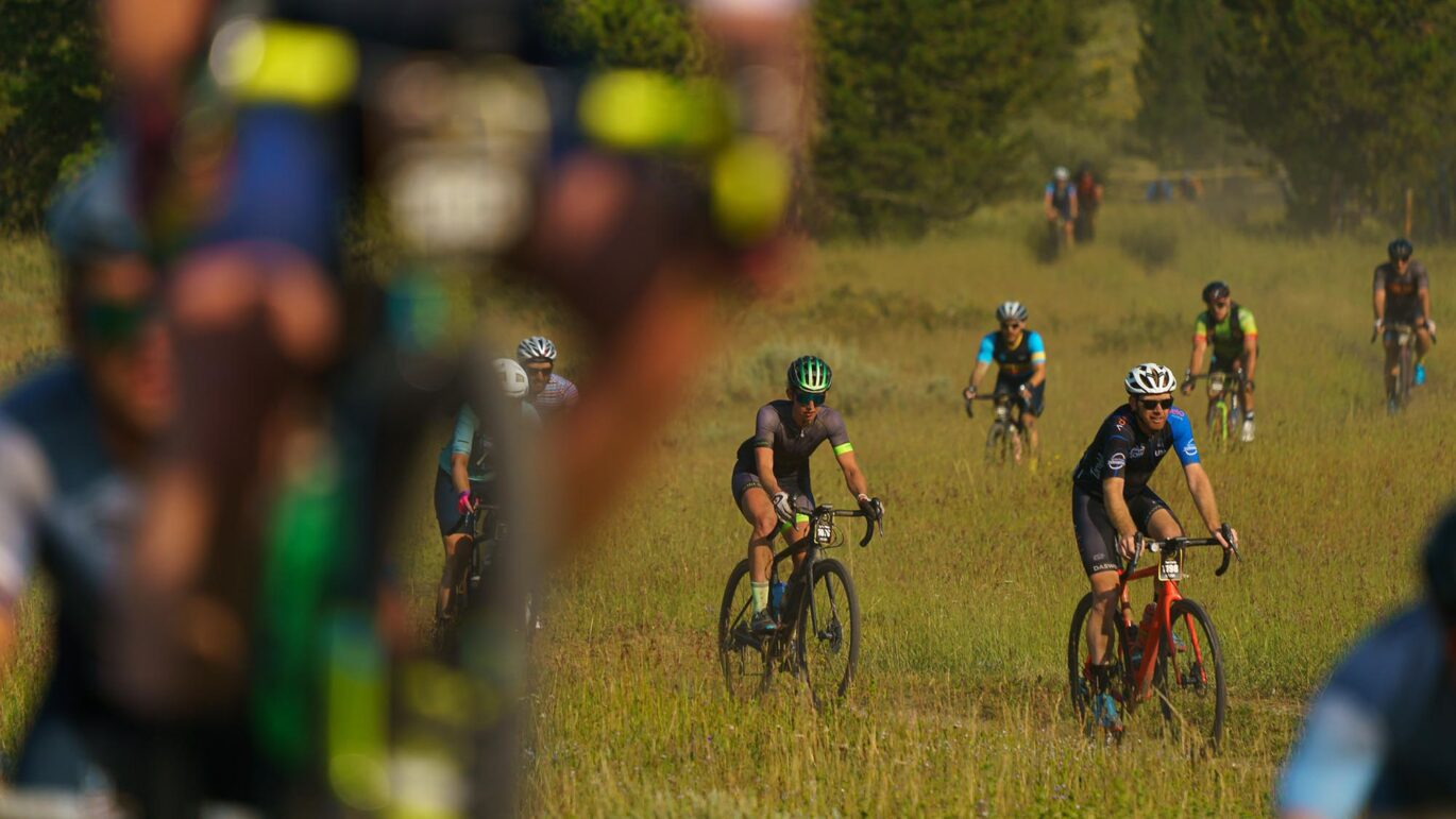 Riders on singletrack in a field while competing at the 2021 SBT GRVL event in Steamboat Springs, Colo.